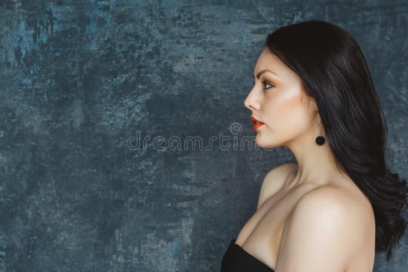 Fashionable ritratto bellissima donna con bruna elegante e labbra rosse Donna con capelli lunghi con orecchini neri Imposta in gr fotografie stock libere da diritti