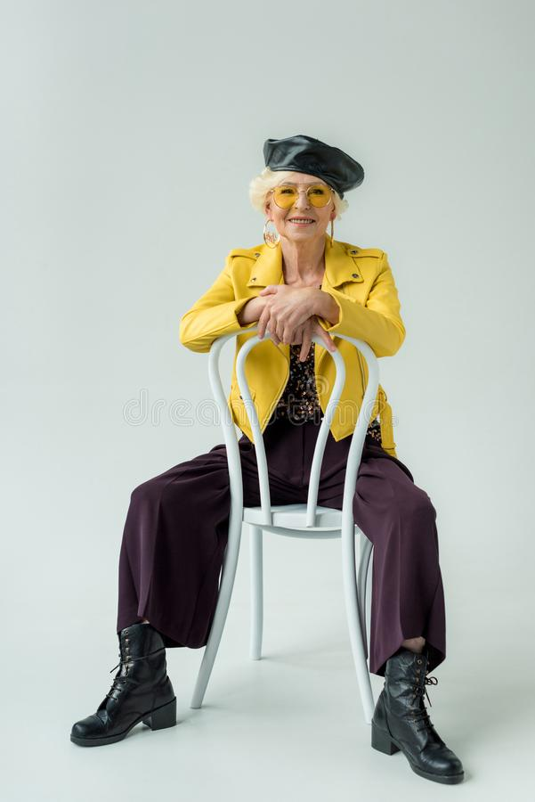 fashionable senior woman in yellow leather jacket and yellow sunglasses sitting on chair, royalty free stock photo
