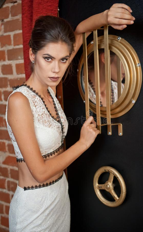 Fashionable sensual attractive lady with white dress standing near a safe in a vintage scene. Short hair brunette woman stock image