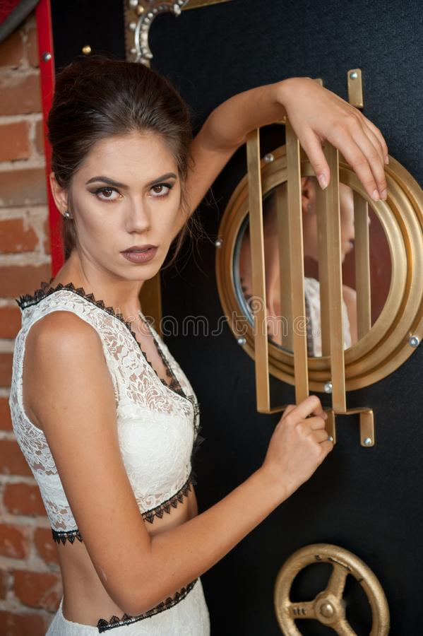 Fashionable sensual attractive lady with white dress standing near a safe in a vintage scene. Short hair brunette woman royalty free stock photography