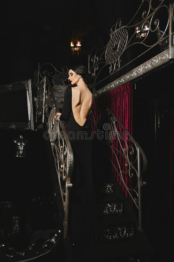 Fashionable and sexy brunette model girl with perfect body and red lips in black evening dress with nude back posing at. Modern luxury interior stock photos