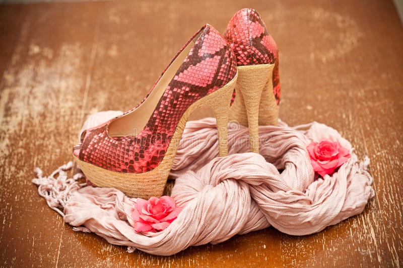 Fashionable shoes pink with pink flowers and a scarf. Stylized snake skin royalty free stock photo