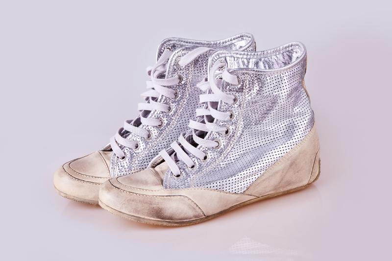 Fashionable silver women`s boots with shoelaces stock photos