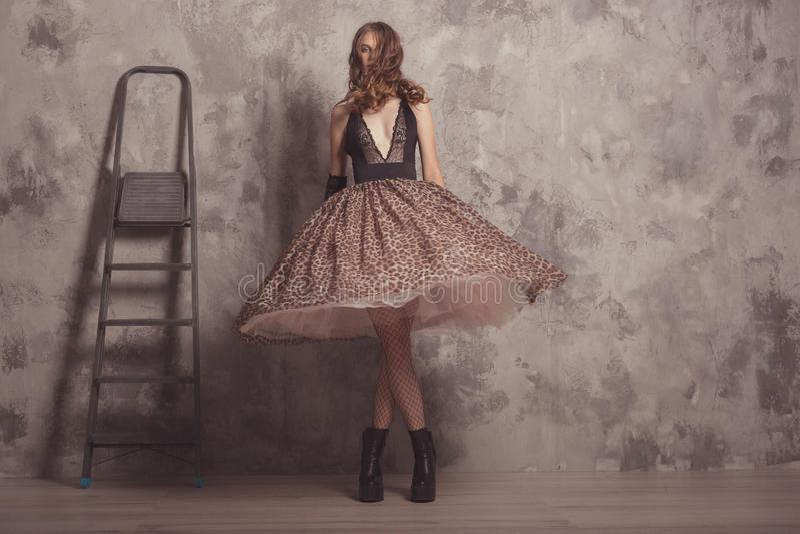 Fashionable självsäker kvinna i kroppsklädd med leopard print, kvinnlig modell i studio med betonbakgrund Vintage-kläder arkivfoto