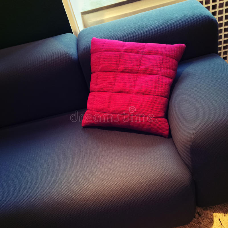 Fashionable sofa with bright red cushion. Fashionable textile sofa with bright red cushion. Stylish furniture royalty free stock photography