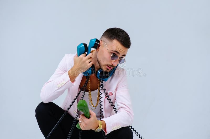 Fashionable sophisticated man in a pink jacket and black trousers, with a lot of handsets, the expression of emotions gestures. Hands space for text stock photos
