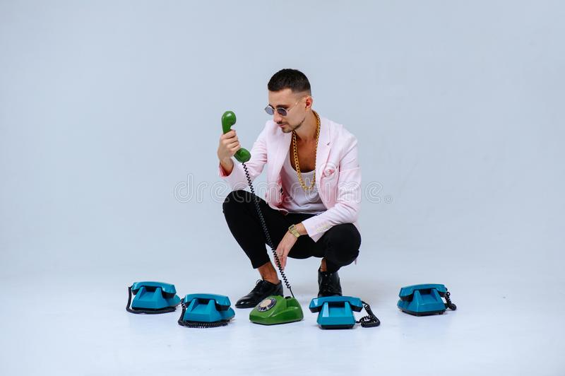 Fashionable sophisticated man in a pink jacket and black trousers, with a lot of handsets, the expression of emotions gestures. Hands space for text stock images