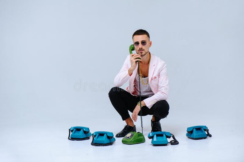 Fashionable sophisticated man in a pink jacket and black trousers, with a lot of handsets, the expression of emotions gestures. Hands space for text royalty free stock images