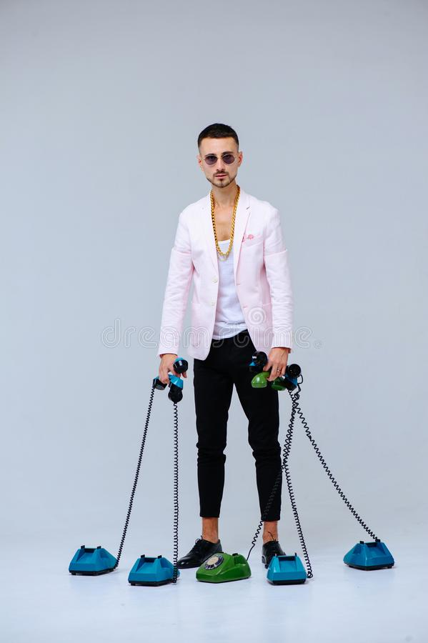 Fashionable sophisticated man in a pink jacket and black trousers, with a lot of handsets, the expression of emotions gestures. Hands space for text royalty free stock image