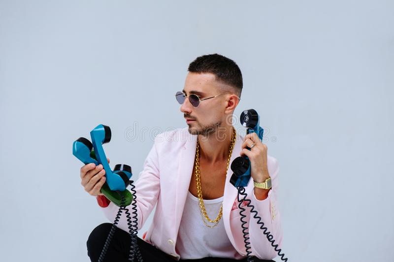 Fashionable sophisticated man in a pink jacket and black trousers, with a lot of handsets, the expression of emotions gestures. Hands space for text stock photo