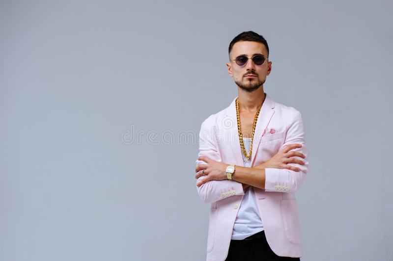 Fashionable sophisticated man in a pink jacket and black trousers, wears a gold chain, the expression of emotions gestures with. His hands stock image