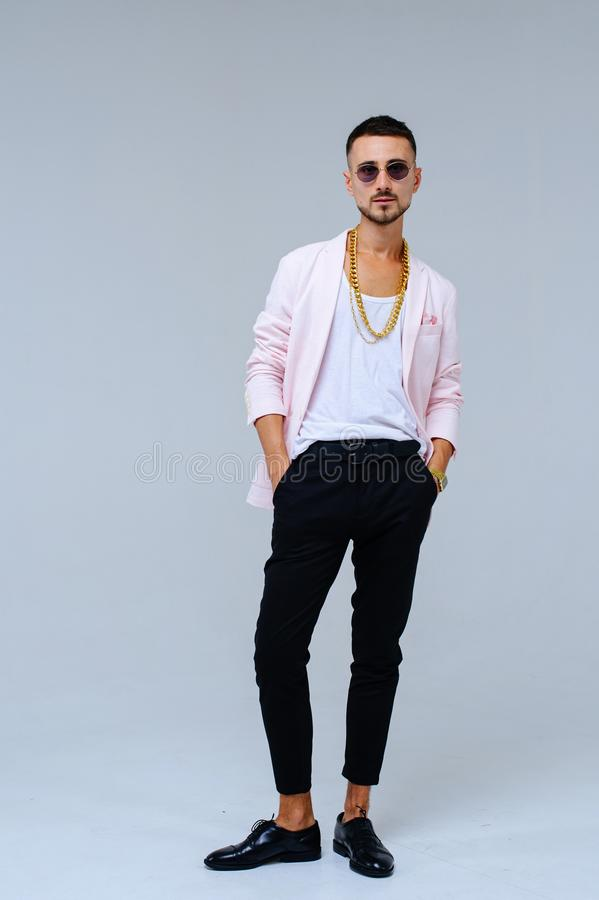 Fashionable sophisticated man in a pink jacket and black trousers, wears a gold chain, the expression of emotions gestures with. His hands stock photo