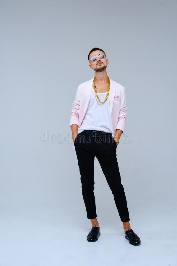 Fashionable sophisticated man in a pink jacket and black trousers, wears a gold chain, the expression of emotions gestures with. His hands royalty free stock photo