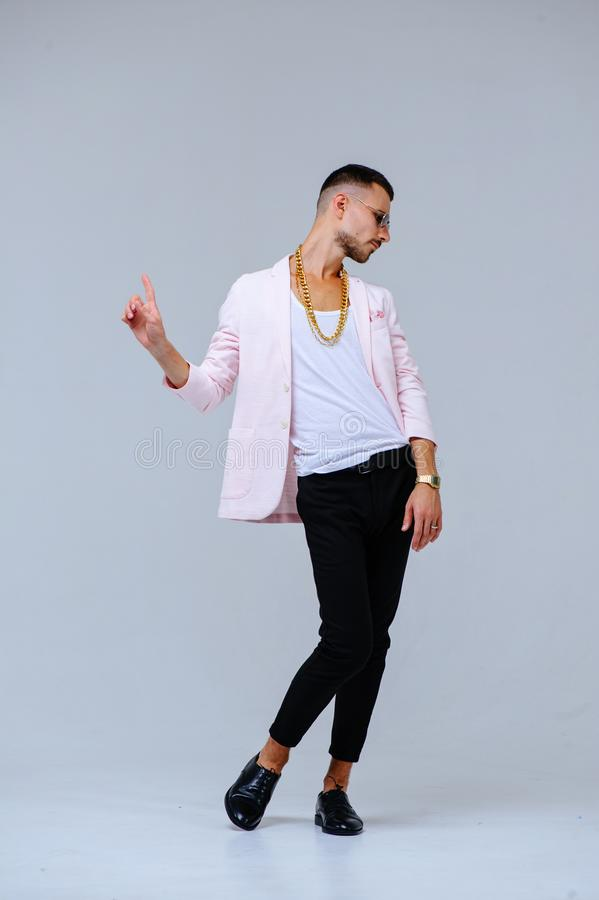 Fashionable sophisticated man in a pink jacket and black trousers, wears a gold chain, the expression of emotions gestures with. His hands royalty free stock photos