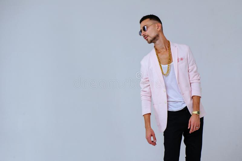 Fashionable sophisticated man in a pink jacket and black trousers, wears a gold chain, the expression of emotions gestures with. His hands royalty free stock photography