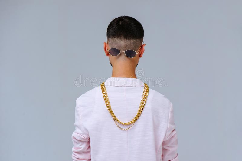 Fashionable sophisticated man in a pink jacket and black trousers, wears a gold chain, the expression of emotions gestures with. His hands royalty free stock images