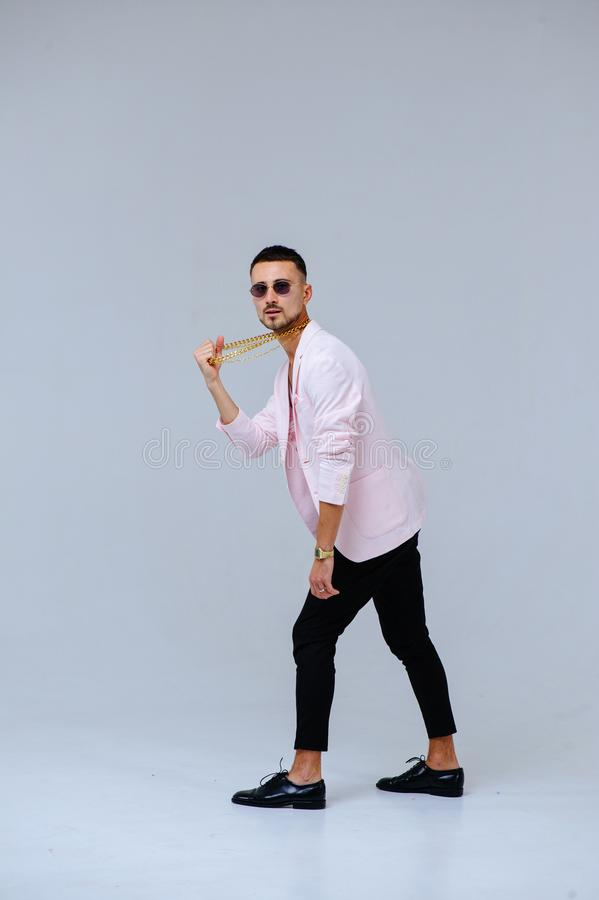 Fashionable sophisticated man in a pink jacket and black trousers, wears a gold chain, the expression of emotions gestures with. His hands stock photography