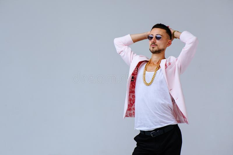 Fashionable sophisticated man in a pink jacket and black trousers, wears a gold chain, the expression of emotions gestures with. His hands stock images