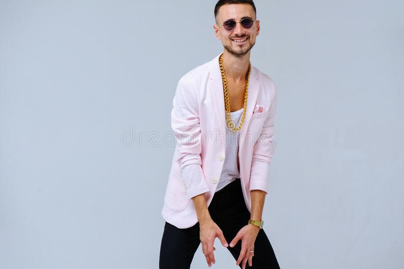 Fashionable sophisticated man in a pink jacket and black trousers, wears a gold chain, the expression of emotions gestures with. His hands stock photos