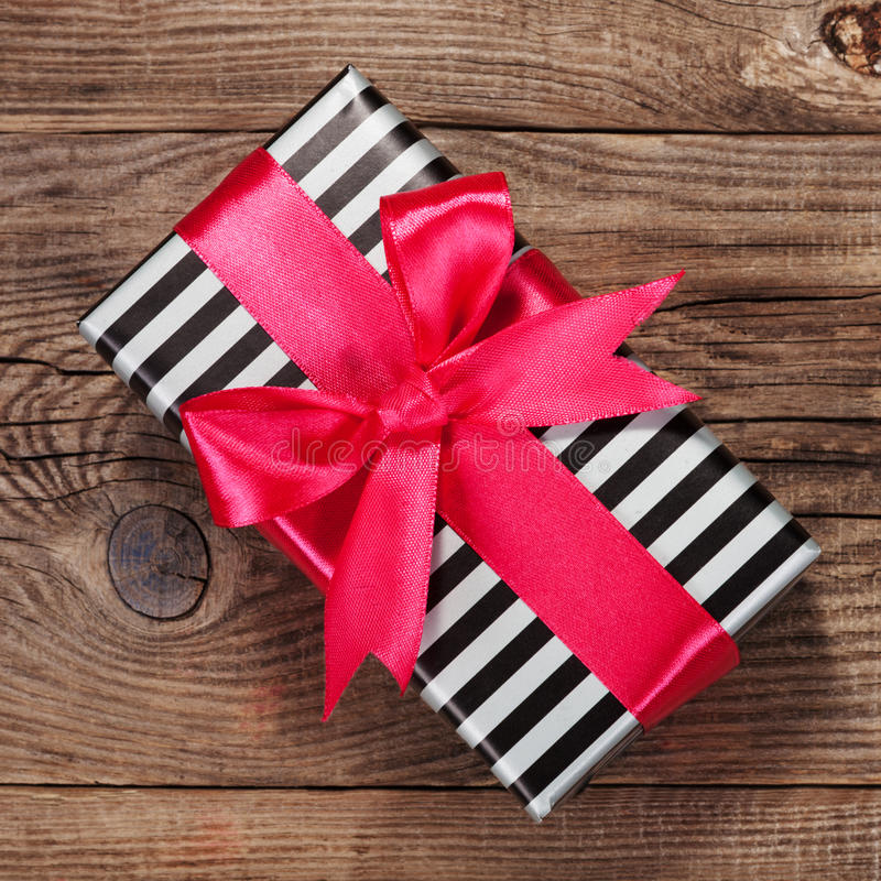 Fashionable striped gift box with a pink bow on board. royalty free stock image