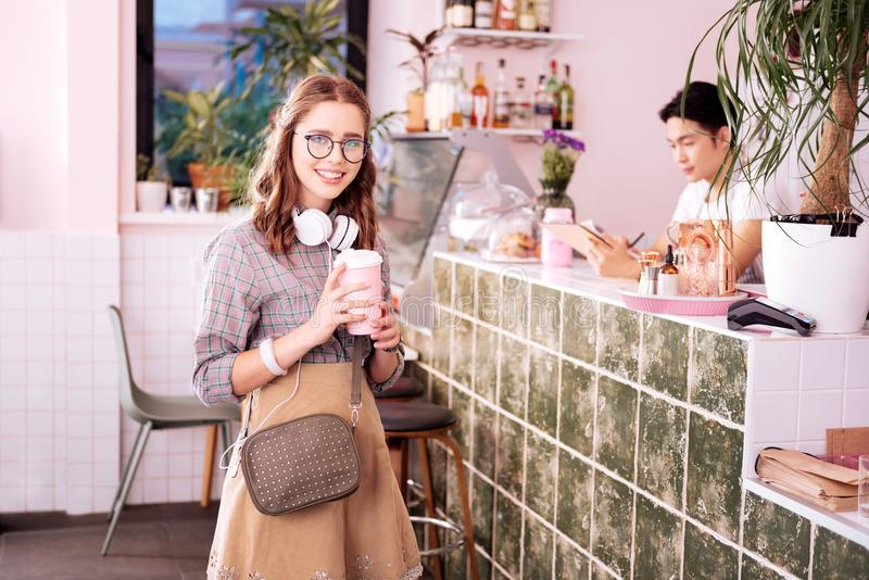 Modern fashionable student wearing glasses standing in coffee shop stock image