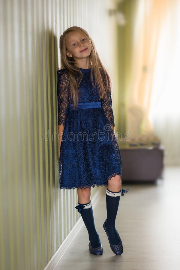 Fashionable style of clothes for children. Little little girl wearing a beautiful lace blue dress. Girl model with long hair stock images
