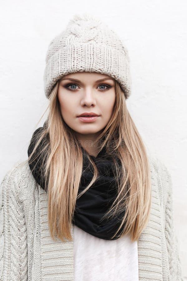 Fashionable stylish girl in white knit jacket. Fashionable stylish girl in white beanie and knit jacket. Outdoors, lifestyle stock photos