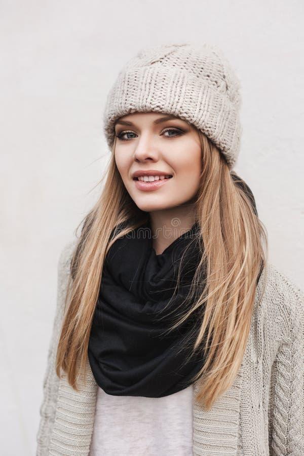 Fashionable stylish girl in white knit jacket. Fashionable stylish girl in white beanie and knit jacket. Outdoors, lifestyle royalty free stock photo