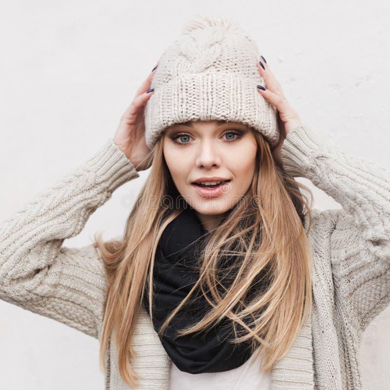 Fashionable stylish girl in white knit jacket. Fashionable stylish girl in white beanie and knit jacket. Outdoors, lifestyle royalty free stock photography