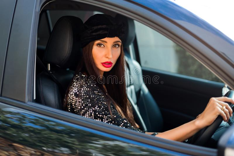 Fashionable stylish lady sits behind the wheel of a car, drives along the road, smiles, looks into the camera, transport, woman royalty free stock images