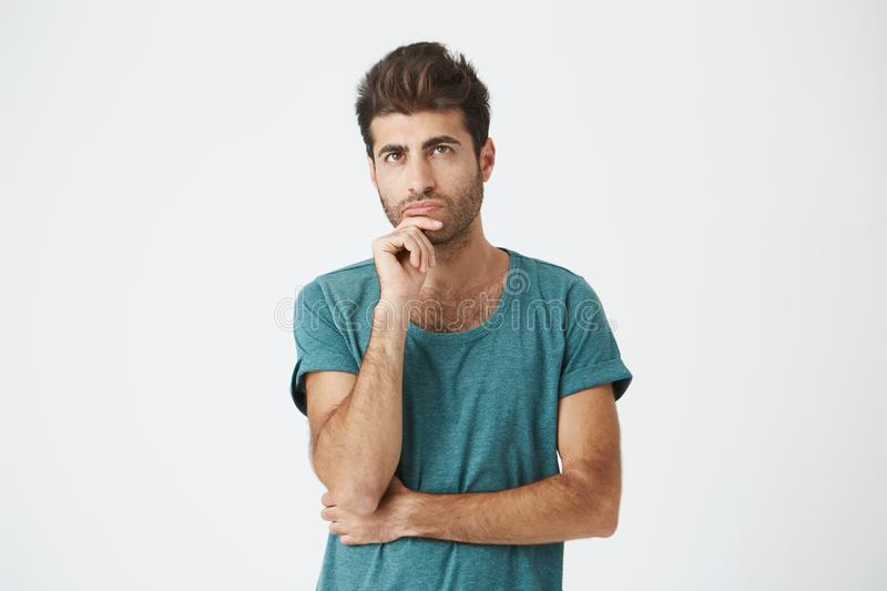 Fashionable, stylish man with dark eyes in casual clothes looking aside with placid and thoughtful look. Pensive guy royalty free stock photography