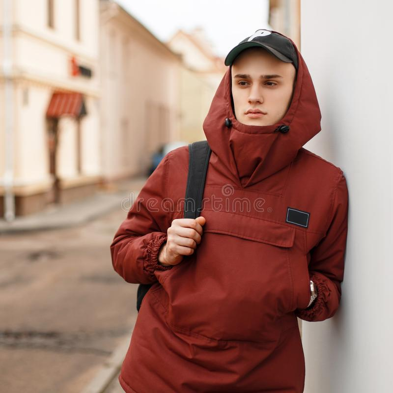Fashionable stylish man in a stylish sports jacket with. A baseball cap with a bag near the wall on the street stock image