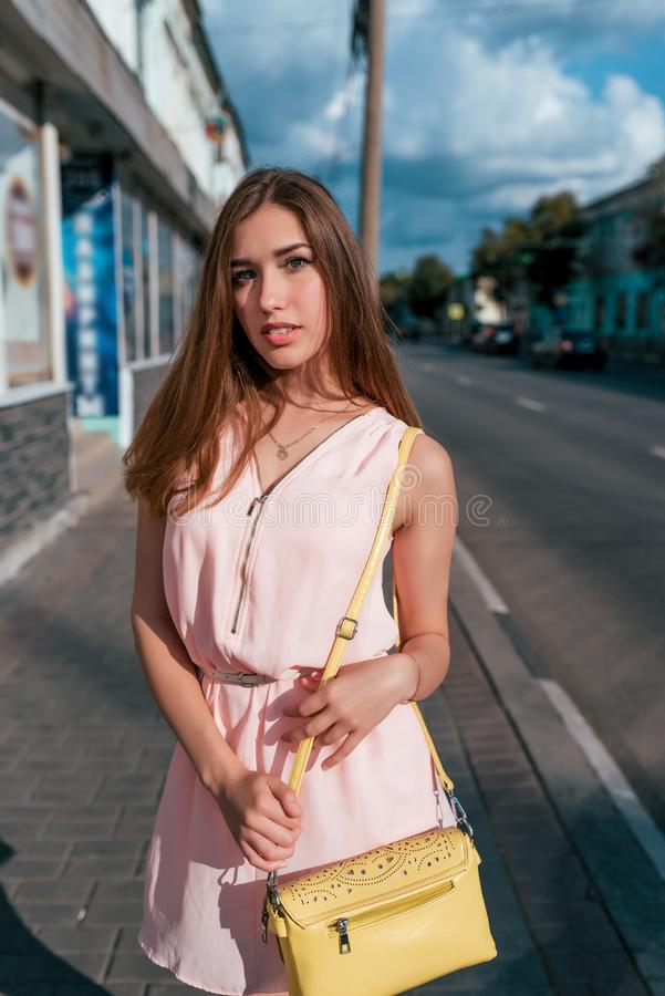 Fashionable and stylish woman, a beautiful girl in a pink dress in summer in city, in hands of a yellow handbag, happy royalty free stock images