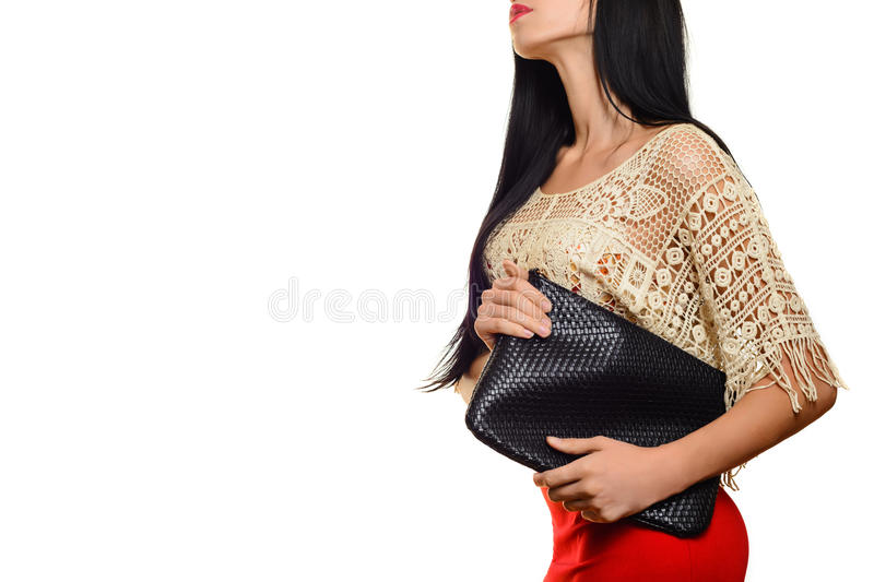Fashionable stylish young woman in red skirt with black clutch stock photography