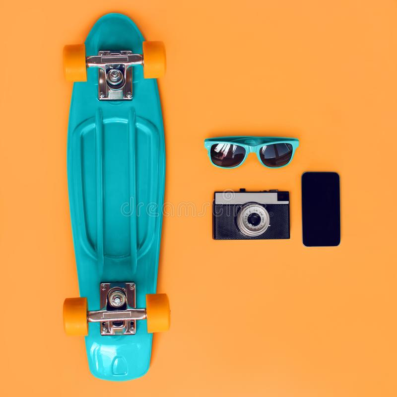 Fashionable summer colorful blue skateboard, sunglasses, vintage film camera, frameless smartphone screen on orange background. Top view, flat lay stock photography
