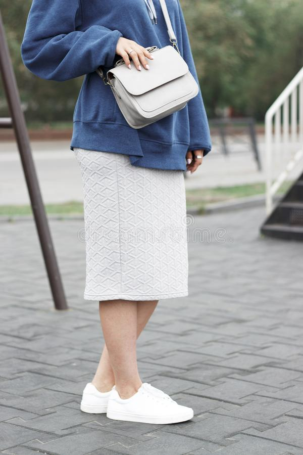 Fashionable summer outfit, a girl in a sweatshirt and white sneakers with bag stock photo