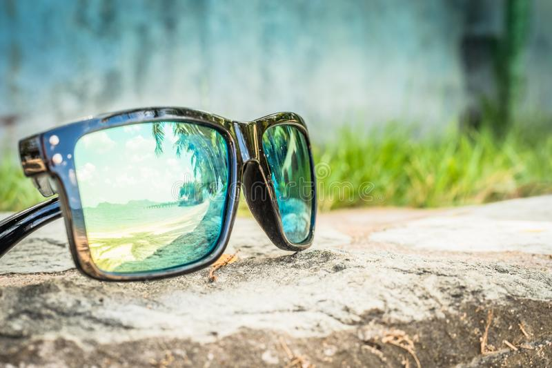 Fashionable sunglasses. Sunglasses with mirrored lenses. Reflection of the beach and tropical palm trees in sunglasses. royalty free stock photo