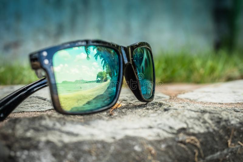 Fashionable sunglasses. Sunglasses with mirrored lenses. Reflection of the beach and tropical palm trees in sunglasses royalty free stock photo
