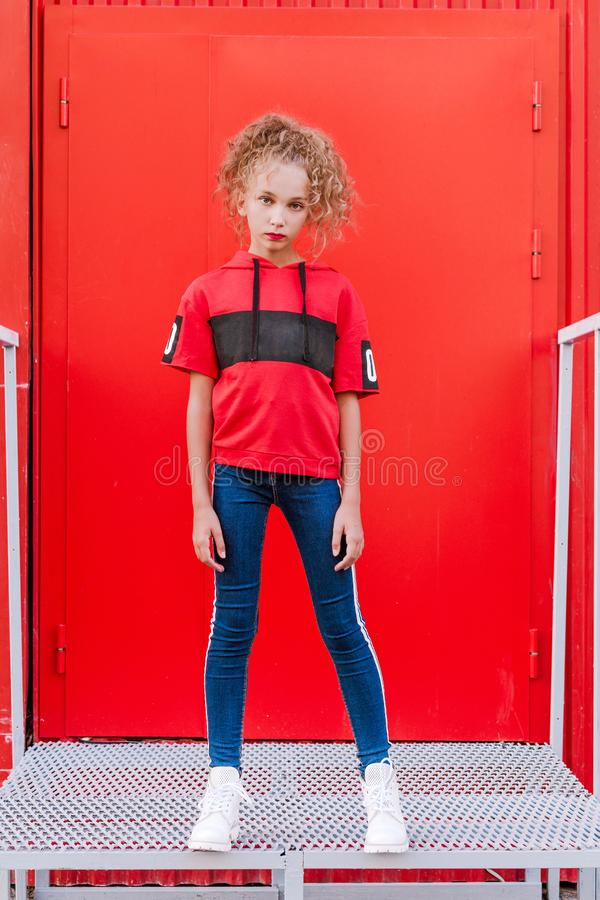 Fashionable teen girl posing against a red wall royalty free stock images