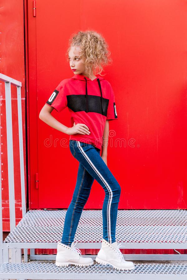 Fashionable teen girl posing against a red wall royalty free stock photos