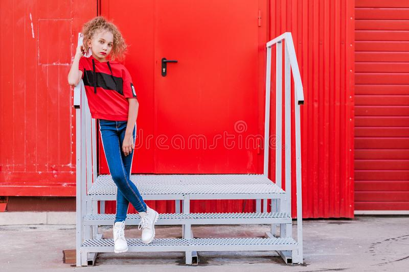 Fashionable teen girl posing against a red wall royalty free stock photography