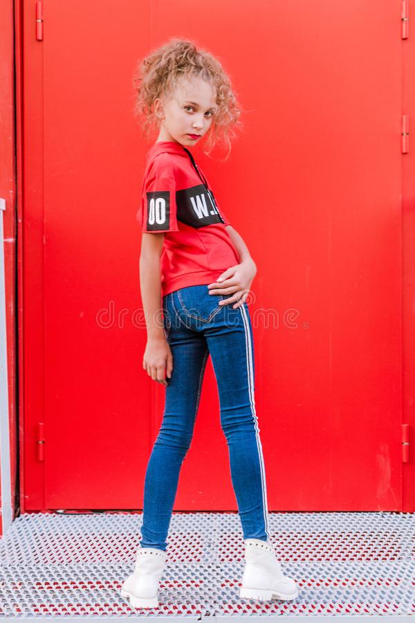 Fashionable teen girl posing against a red wall stock photo