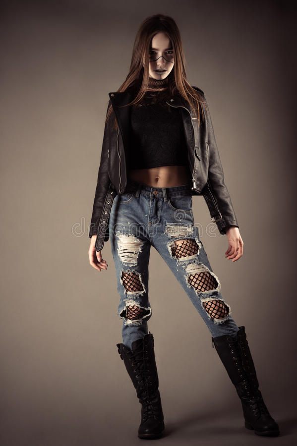 Fashionable teenager girl in leather jacket and torn jeans stock photo
