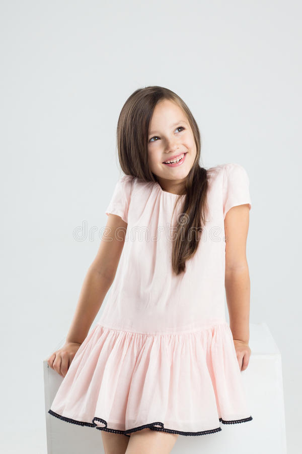 Fashionable teenager girl in pink dress smiles stock image