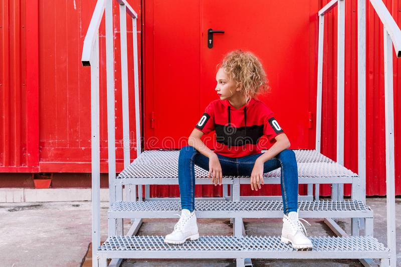 Fashionable teenager girl posing on a red wall background, sitting on the stairs royalty free stock images
