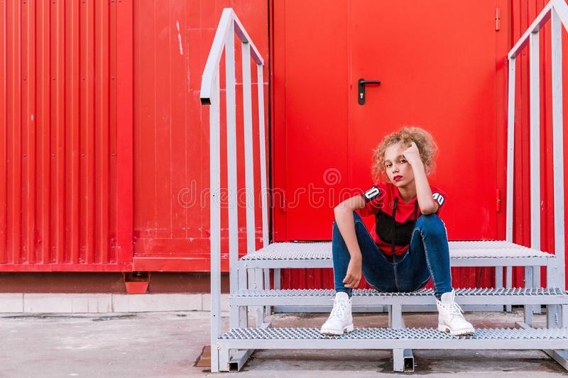 Fashionable teenager girl posing on a red wall background, sitting on the stairs stock images