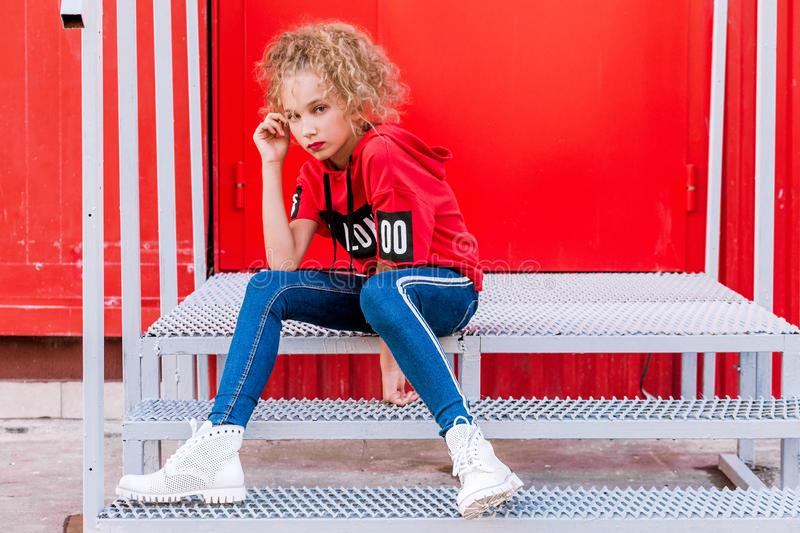 Fashionable teenager girl posing on a red wall background, sitting on the stairs royalty free stock photography