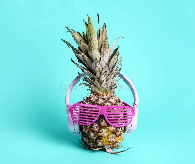 Fashionable trendy pineapple fruit with headphones and sun glasses listen to the music over bright pastel cyan background stock photos