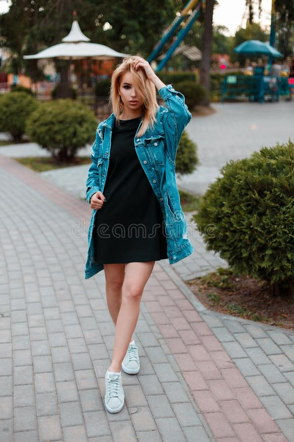 Fashionable urban cute young woman in a black stylish dress in a trendy long denim jacket in white sneakers posing in a park royalty free stock photos