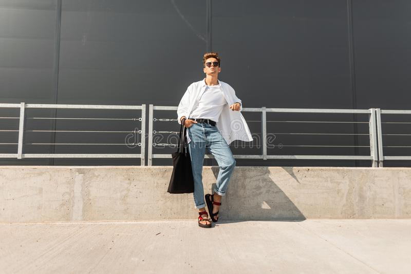 Fashionable urban young man in red sandals in a white shirt in blue jeans in sunglasses with a black bag relaxes in the street. On a bright sunny day. Stylish royalty free stock photos